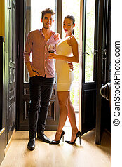 A young couple standing at the door