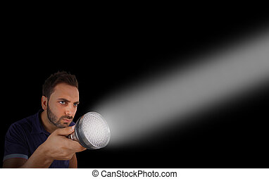 Man with a flashlight in the dark - Young man with a...