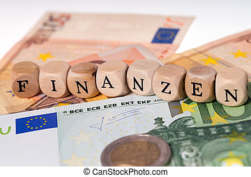Finance - Banknotes and wood cubes with the german word...