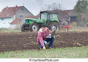 Farmer with laptop - Young farmer with laptop on the field...