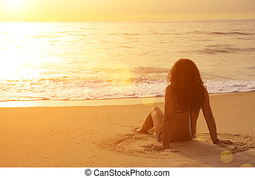 Sitting in the Sand - Young woman sitting in the sand...