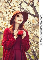 mujeres, en, rojo, suéter, y, sombrero, con, taza,