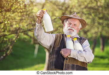 Farmer with milk bottles - Senior farmer with milk bottles...