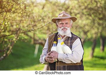 Farmer with milk bottles - Senior farmer with milk bottles...