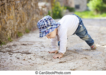 Little boy crawling on stone paved sidewalk - Cute little...