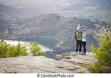 Young couple with toddler boy standing on cliff and smiling