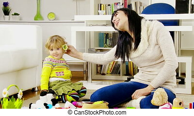 woman with baby daughter playing