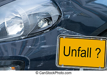 broken car and sign with the german word accident