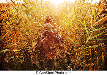 soldier aiming with rifle   and wading through thickets
