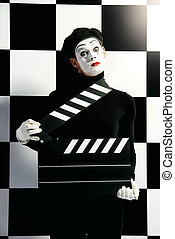 mime - Movie actor and a mime posing with clapper board with...