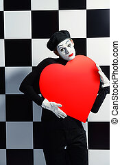 mime - Portrait of a male mime artist holds large red heart...