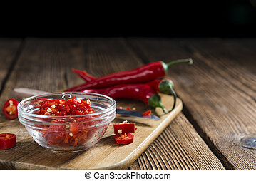 Cutted red Chilis (close-up shot) on wooden background