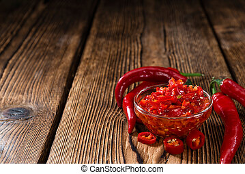 Preserved red Chilis close-up shot on wooden background