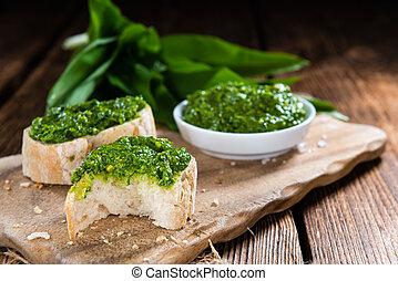 Bowl with homemade Ramson Pesto (close-up shot) on wooden...