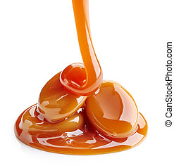 caramel candies and sauce isolated on white background