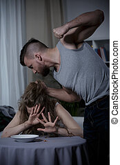 Man terrorizing his wife - Young strong muscular man...