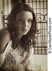Woman - pretty woman lying on a bed in sephia