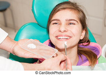 Patient - Young patient is being treated at a dentist office...