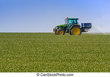 Tractor with worker spraying green field on spring
