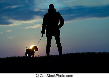 Silhouette of man and dog - Silhouette of young man in...