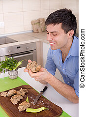 Man eating wholemeal bread - Young attractive man holding...
