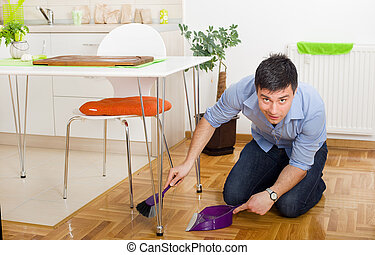 Man cleaning in kitchen - Young man on knees holding broom...