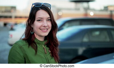 Young woman holding keys to new car and smiling at camera HD