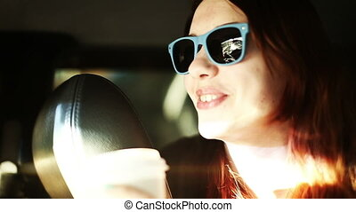 Smiling lifestyle portrait of laughing woman in sunglasses inside a car joy ride