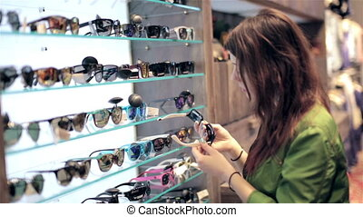Young couple shopping in store, looking for sunglasses,...