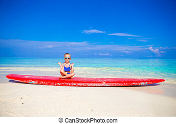 Little girl in yoga position meditating on surfboard -...