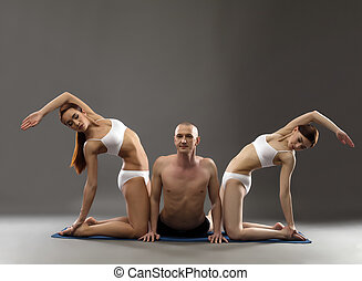 Image of man and girls practicing yoga threesome, on gray...