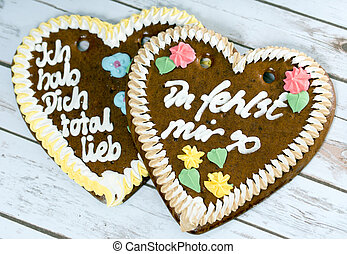 Love - two gingerbread hearts over a wooden background