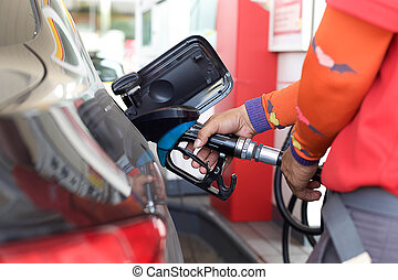 Pumping gas into a car in gas station