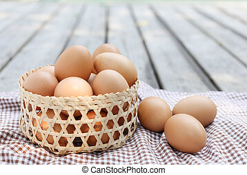 Eggs in the basket on wooden decking