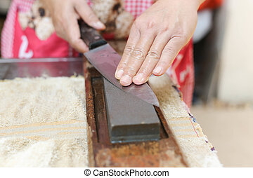 Hand working Thai chef shapen knife with  stone
