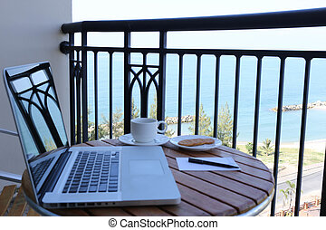 Focus on ocean and computer laptop on balcony and coffee -...