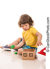 Toddler boy playing with wood house toy adding cubes