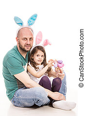 Cheerful father and daughter with bunny ears holding Easter...