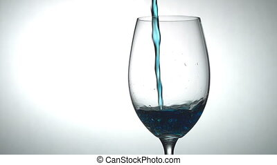 Blue Alcoholic Beverage - In a tall glass slowly pouring jet...