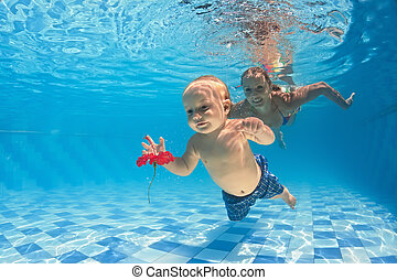 Baby underwater swimming lesson with instructor in the pool...