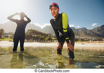 Triathlon training at the lake - Confident young woman in...