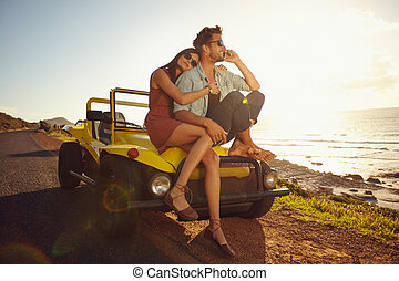 Young couple on road trip Young couple sitting on the