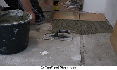 man tile cement laser - zoom in of man straighten tile on...