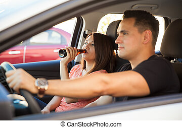 Latin couple drinking in a car - Profile view of a young...