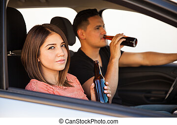 Drinking beer inside a car - Portrait of a young Hispanic...