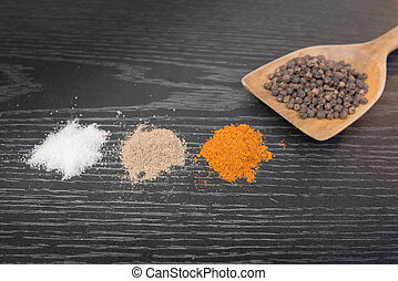 assorted spices and condiments on table black wooden