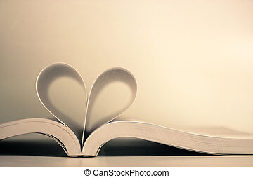 Opened book with heart page against blank background