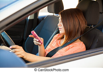 Woman texting and driving - Reckless young brunette using a...