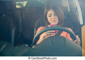 Texting behind the wheel - Portrait of a young woman texting...
