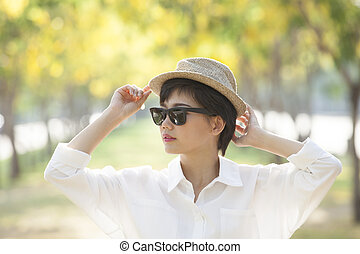 portrait of young beautiful asian woman wearing sun glasses...